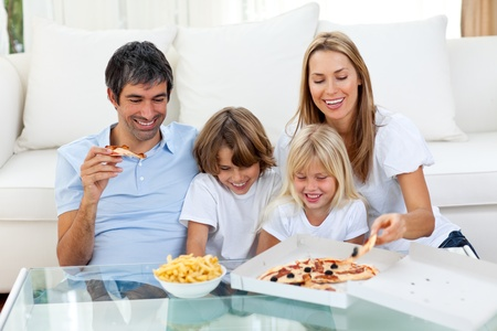 mealtime: Positive family eating pizzas  Stock Photo