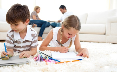 Cute siblings drawing lying on the floor Stock Photo - 10256844