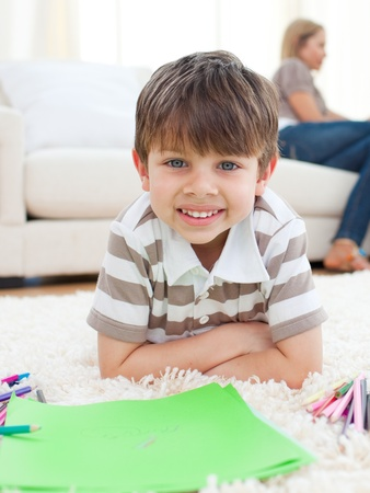 Portrait of little boy drawing lying on the floor photo