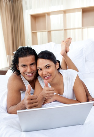 Couple with thumbs up using a laptop photo
