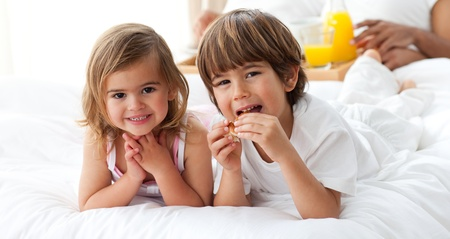 Cute brother and sister having breakfast  photo