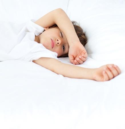 nio durmiendo: Lindo ni�o acostado en la cama de los padres Foto de archivo
