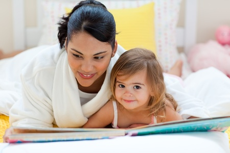 stories: Cute little girl reading a book with her mother