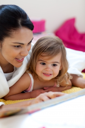 Caring mother reading a book with her girl photo