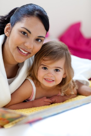 Close-up of a beautiful little girl and her mother reading a book photo
