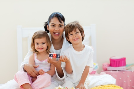 Attractive mother and her children playing with letters blocks photo