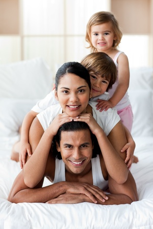 Young family having fun on the bed  Stock Photo - 10258999