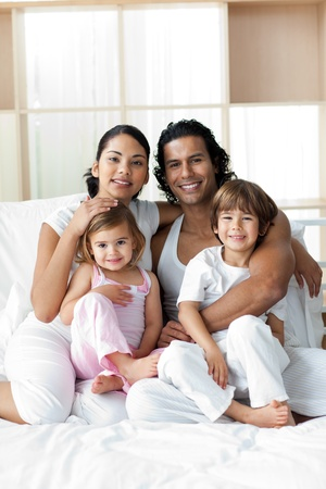 Portrait of a smiling family sitting on the bed photo