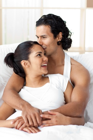 Young man kissing his girlfriend lying on the bed Stock Photo - 10259035