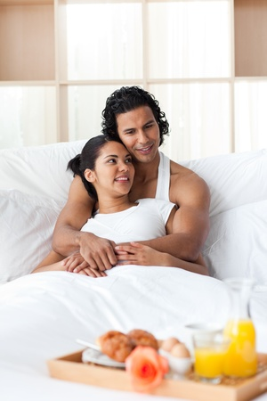 Lovers having breakfast lying on the bed  photo