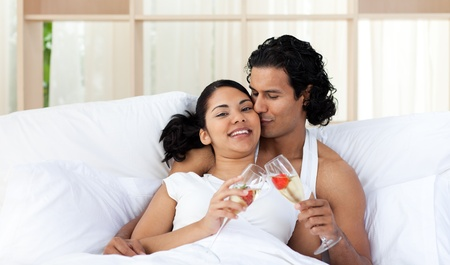 Lover kissing his wife while toasting with Champagne photo