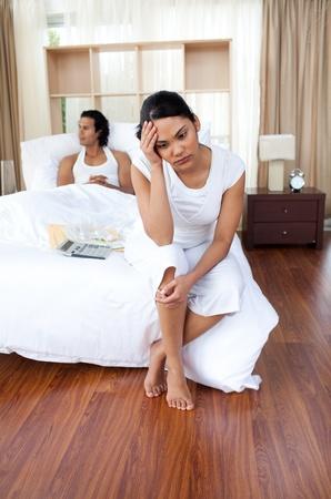 novios enojados: Amantes de la joven sentada en la cama por separado Foto de archivo