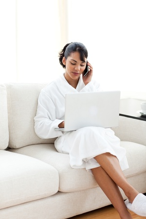Attractive woman on phone using a laptop photo