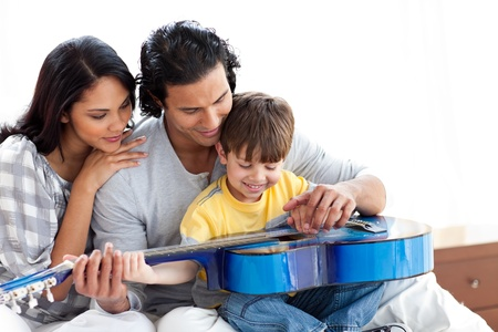 Happy little boy playing guitar with his parents photo