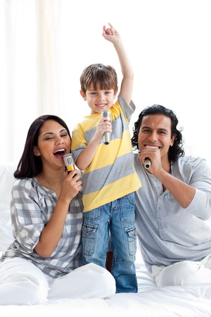 child singing: Lively young family singing with microphones