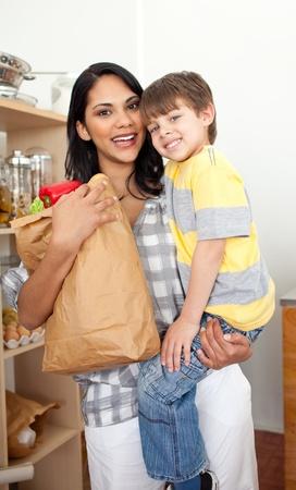 bolsa supermercado: Adorable Little boy desempaquetado ultramarinos bolsa con su madre Foto de archivo