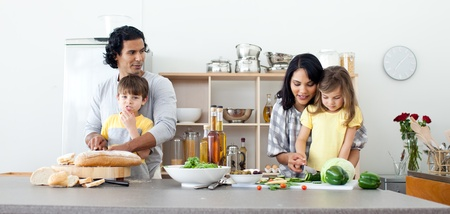 family in kitchen: Portrait of a family preparing lunch Stock Photo