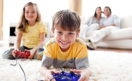 Cute little boy playing video game with his sister Stock Photo - 10245056