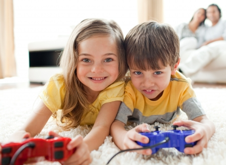 Adorable siblings playing video game  photo