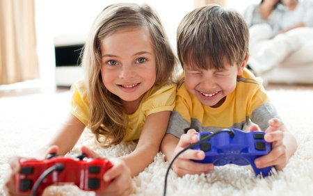 game room: Brother and sister playing video game  Stock Photo