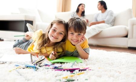 frau sitzt am boden: Adorable Btother und Schwester Zeichnung auf dem Boden liegend Lizenzfreie Bilder