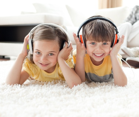 Smiling siblings listening music with headphones photo