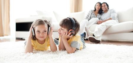 listening to music: Ni�o y ni�a jugando en el piso con auriculares Foto de archivo
