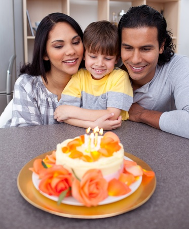 Little boy celebrating his birthday with his parents photo