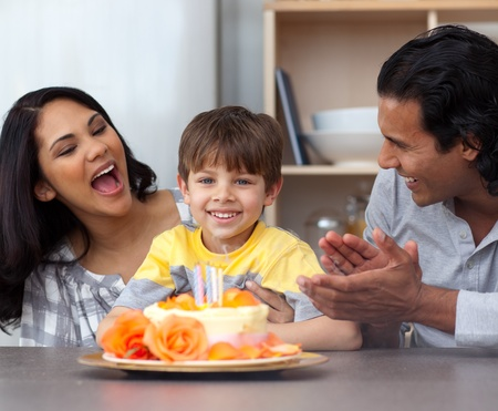 Smiling little boy celebrating his birthday with his parents photo