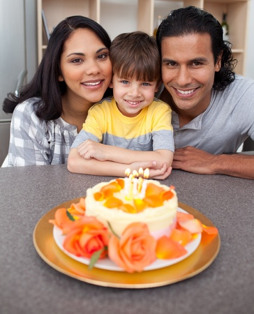 Attentive parents celebrating their sons birthday in the kitchen photo