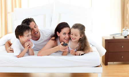 Joyful family having fun in the bedroom photo