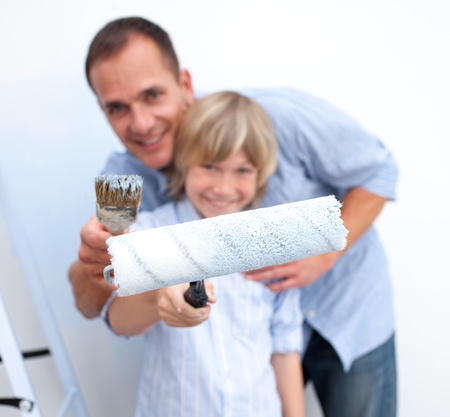 Close-up of a father and his son holding paintbrush  photo
