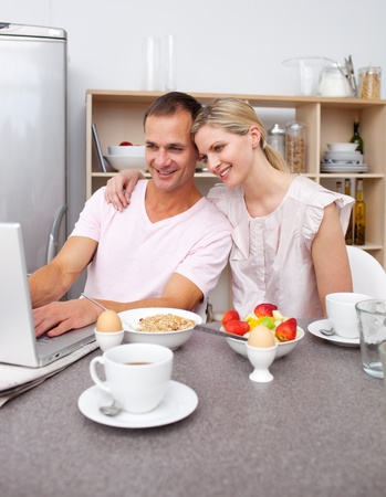 Enamored couple using a laptop while having breakfast  photo