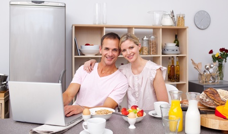 Young couple using a laptop while having breakfast  photo