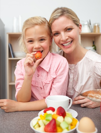 Attentive mother eating fruit with her daughter  photo