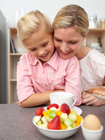 Adorable little girl eating fruit with her mother  photo