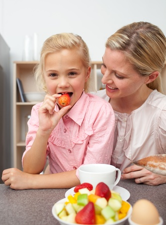 Attractive mother eating fruit with her daughter  photo
