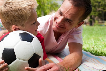 Close-up of an attentive father and his son holding a soccer ball  photo