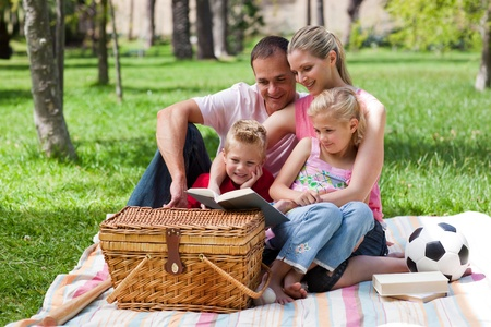 Happy family reading in a park photo