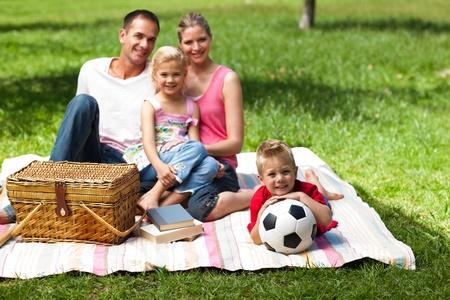 disfrutar: Padres e hijos relajantes en un picnic