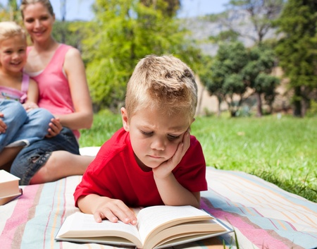 Serious little boy reading while having a picnic with his family  photo