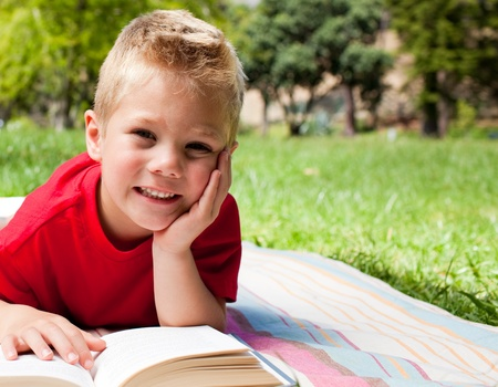 Cute little boy reading at a picnic  Stock Photo