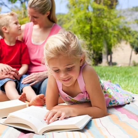 Concentrated blond girl reading while having a picnic with her family