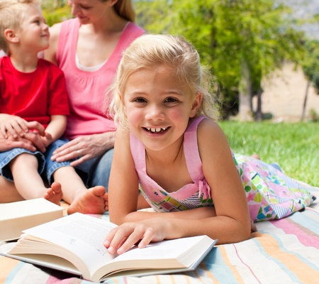 Close-up of a little girl reading at a picnic  photo