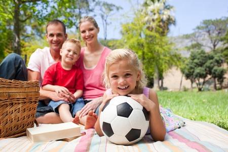 niños jugando en el parque: Niña rubia sosteniendo un balón de fútbol en un picnic  Foto de archivo