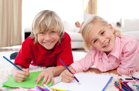 Smiling children drawing lying on the floor photo