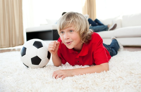 lying on couch: Excited boy watching football match lying on the floor  Stock Photo
