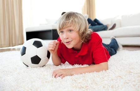 Opgewonden boy kijken voetbalwedstrijd op de grond liggen