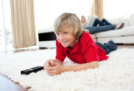 Concentrated boy watching TV lying on the floor  photo