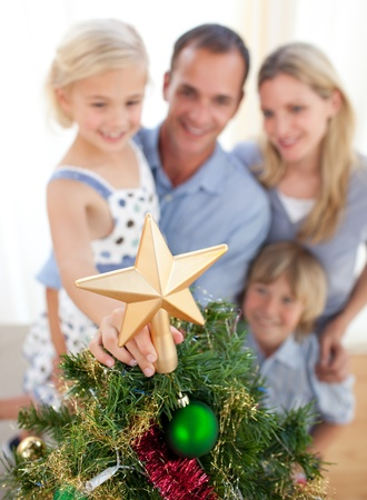 Father lifting his daughter to put the Christmas star on top of the tree photo